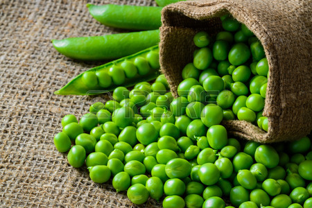 41256287-hearthy-fresh-green-peas-and-pods-on-rustic-fabric-background